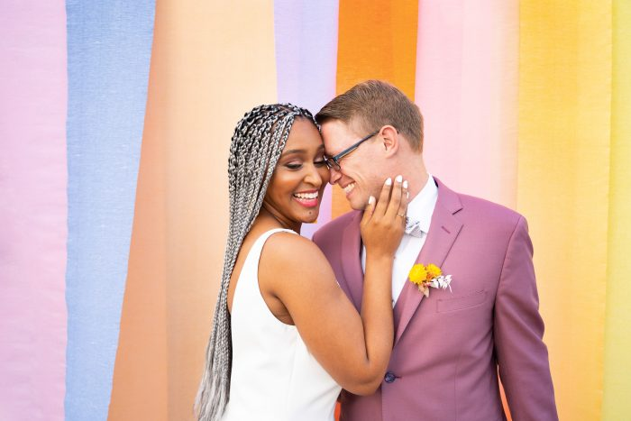 Groom with Real Bride Wearing Maggie Sottero Wedding Dress in Front of Color Block Backdrop at Wedding Ceremony
