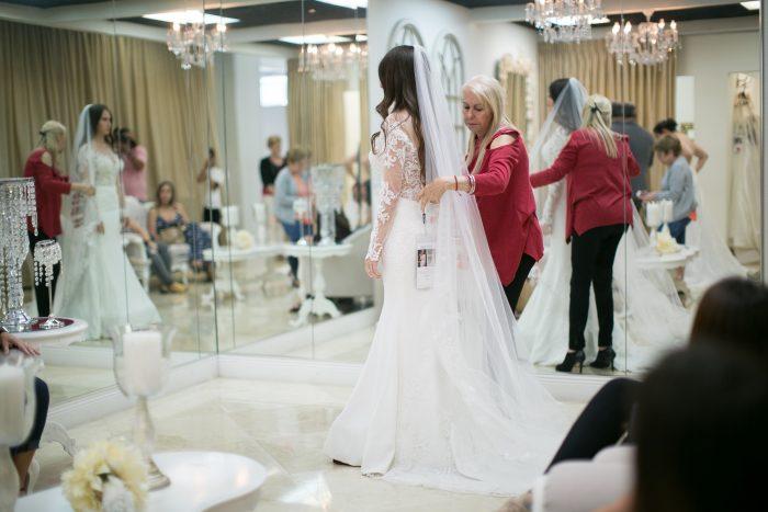 Bridal Consultant Adjusting Veil on Bride