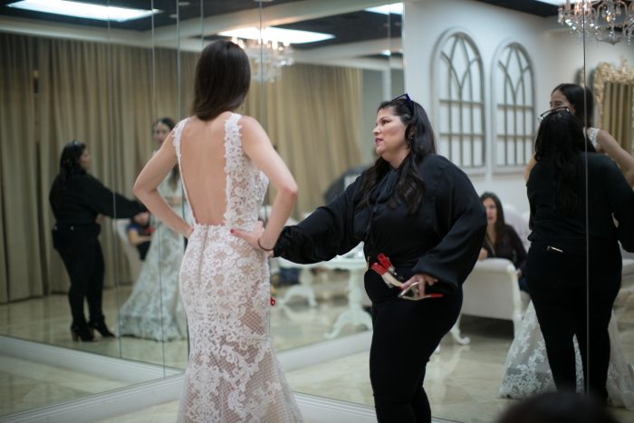Bridal Consultant Helping Bride Try on Wedding Dress by Maggie Sottero
