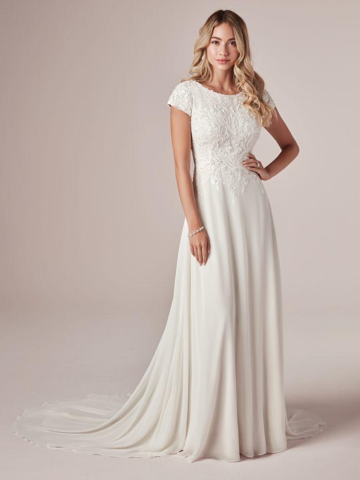 Model Wearing Cap-Sleeve Modest Sheath Wedding Dress Called Mercy Leigh by Rebecca Ingram