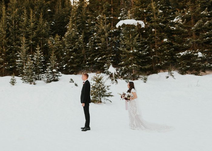 Groom During First Look with Bride Wearing Modest Sleeved Wedding Dress in the Snow