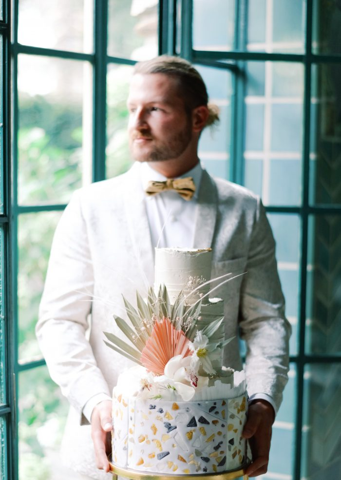 Groom in Tan Suit Holding Geometric Boho Wedding Cake