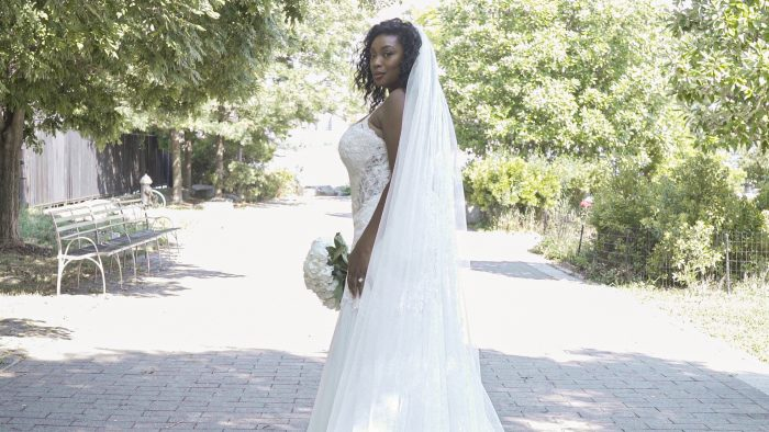 Plus Size Model Wearing Strapless Curvy Wedding Dress with Veil Called Halle by Maggie Sottero