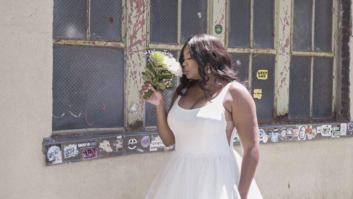 Plus Size Model Wearing Curvy Minimalist Ball Gown Wedding Dress Called Rosemary by Rebecca Ingram