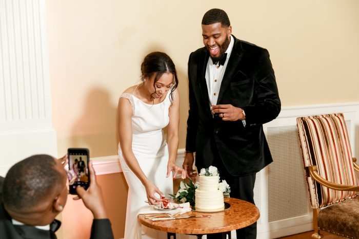 Groom with Bride Cutting White and Classic Wedding Cake at Real Wedding Reception