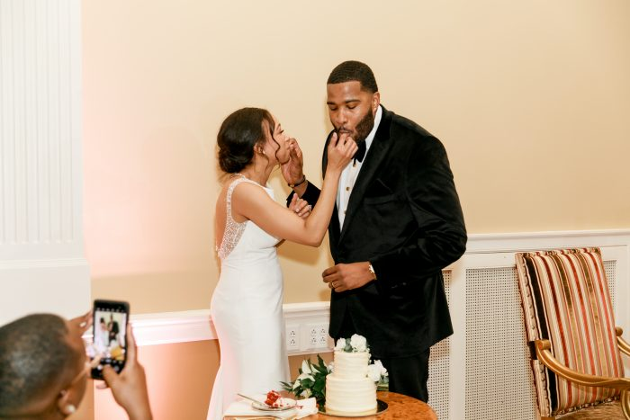 Real Bride and Groom Feeding Each Other Wedding Cake at Real Wedding Reception