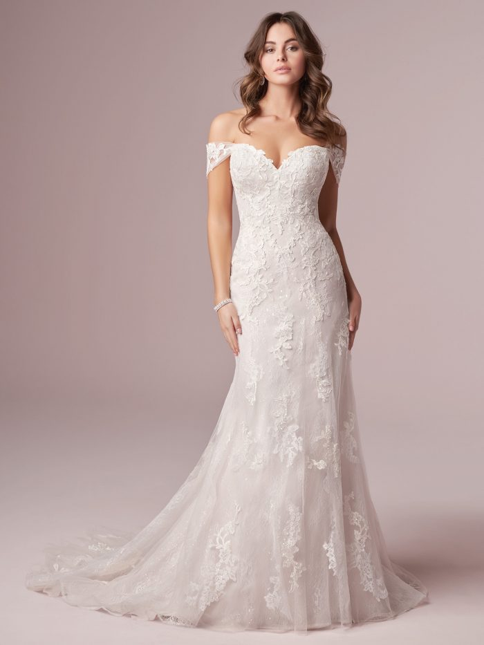 Model Wearing Off-the-Shoulder Floral Sheath Wedding Gown Called Florina by Rebecca Ingram