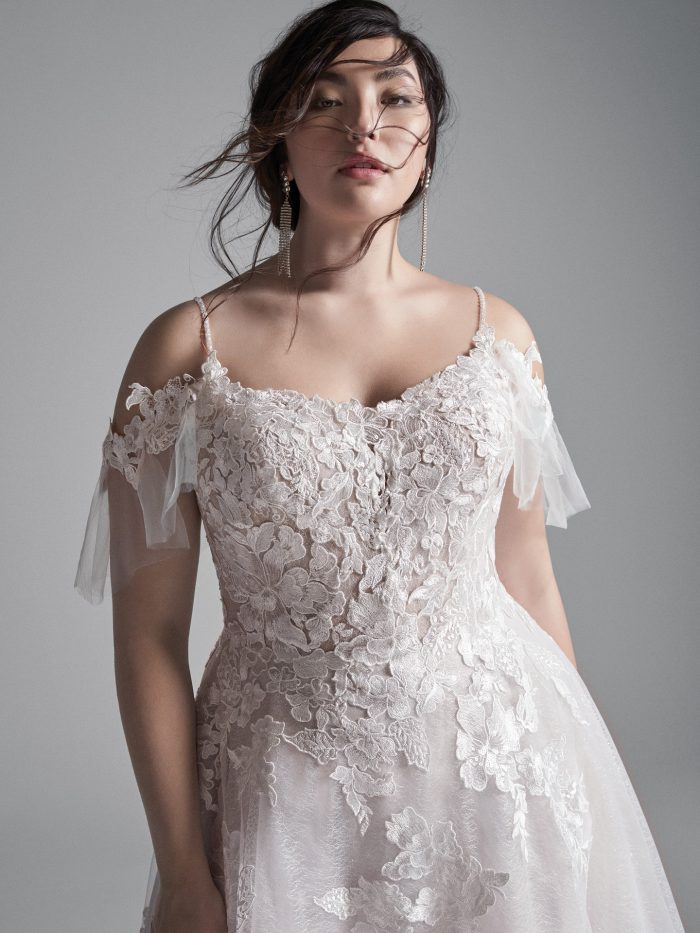 Plus Size Model Wearing Plus Size Cold Shoulder Floral Lace A-line Wedding Gown Called Houston by Sottero and Midgley