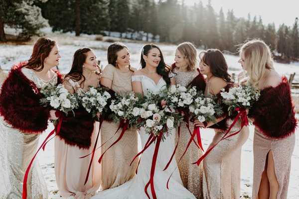Real bride and bridesmaids holding bouquet of roses