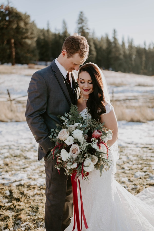 Real Bride Wearing Wedding Dress by Maggie Sottero holding bouquet of roses