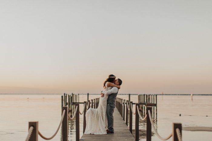 Groom Holding Real Bride on Dock at Beach Wedding