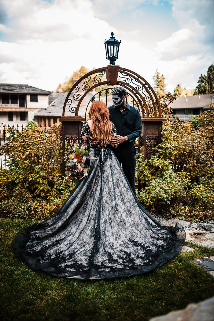 Bride and Groom with painted skull faces outdoors featuring Zander Black Wedding Dress by Sottero and Midgley
