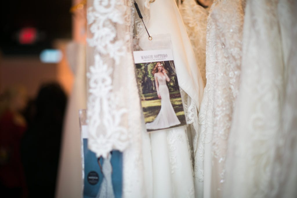 Tag of Maggie Sottero Wedding Dress Hanging from Rack of Wedding Dresses