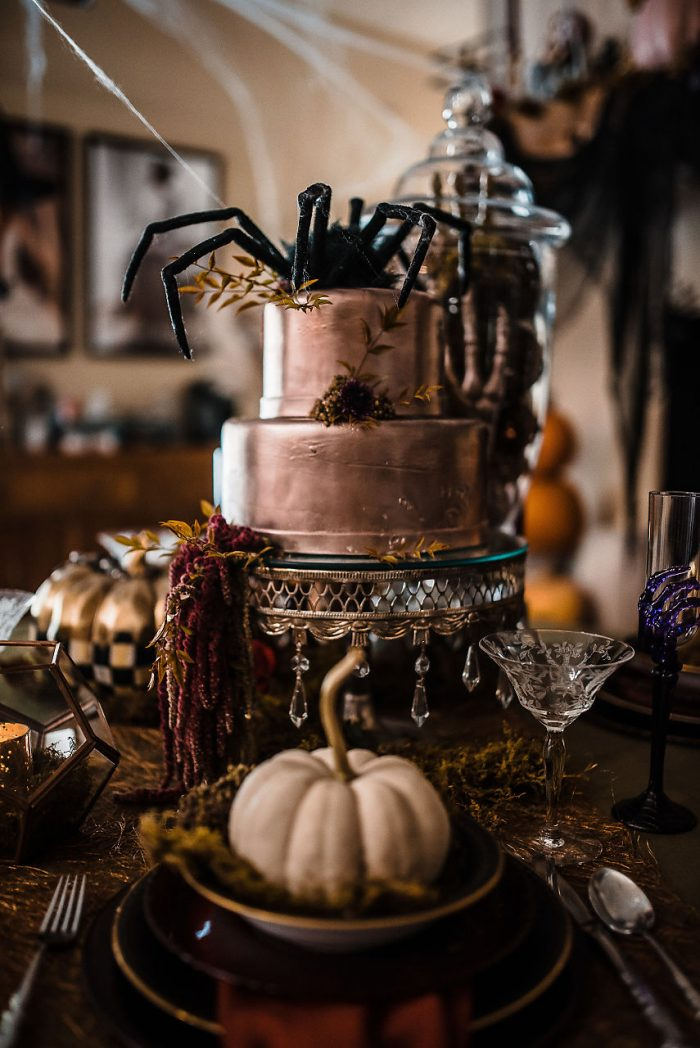 Metallic Halloween Wedding Cake Surrounded by Pumpkins and Spiders