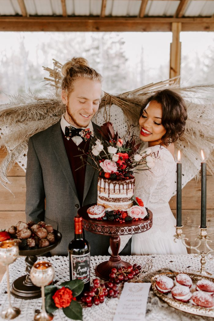 Bride and Groom Standing Behind Vintage Dessert Table with Red Velvet Wedding Cake on a Stand
