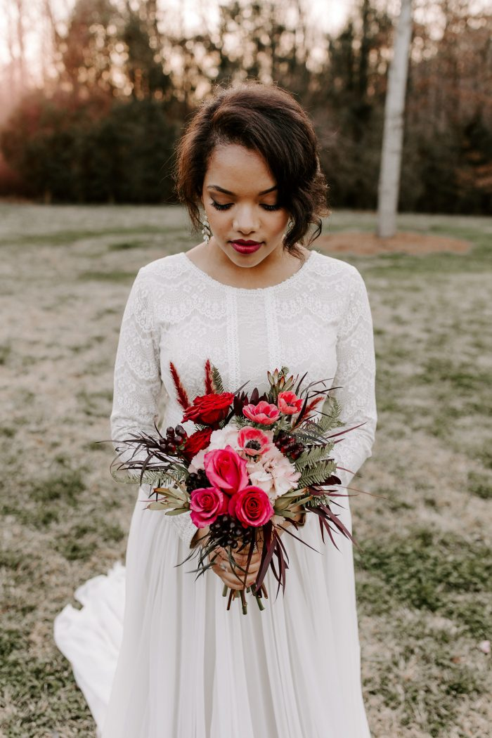Bride Holding Red Bouquet and Wearing Boho Sleeved Wedding Dress Called Deirdre Marie by Maggie Sottero
