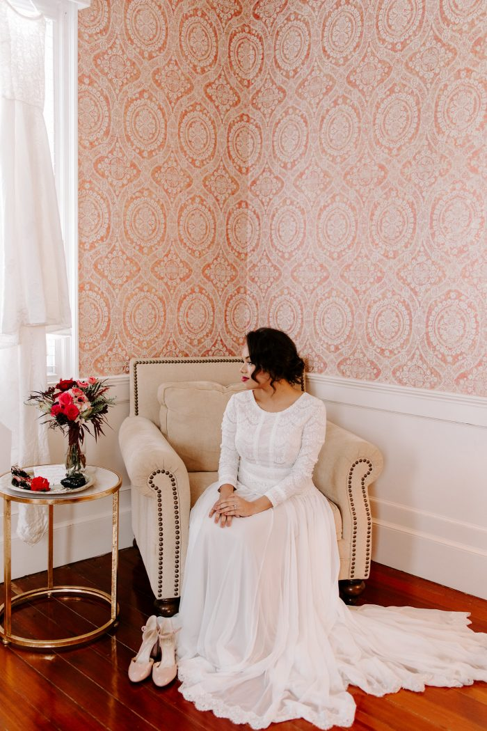 Bride Sitting and Wearing Sleeved Boho Wedding Dress Called Deirdre by Maggie Sottero with Pink Wedding Shoes on the Side