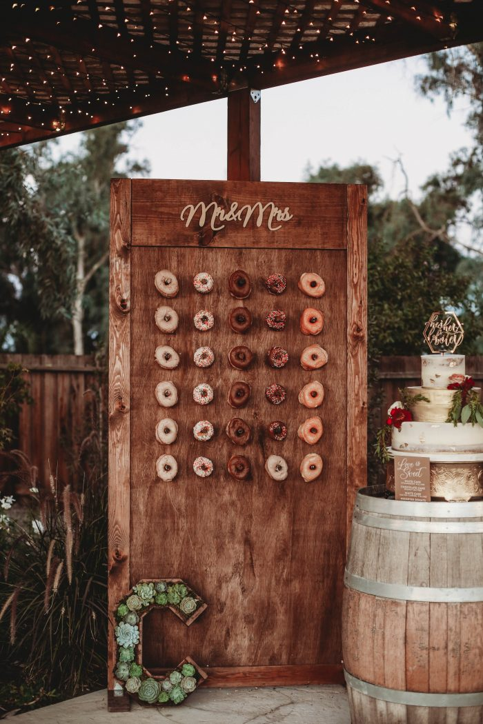 Donut Wall Next to Cake Featuring Fall Wedding Color Palette of Earthy and Gold Tones