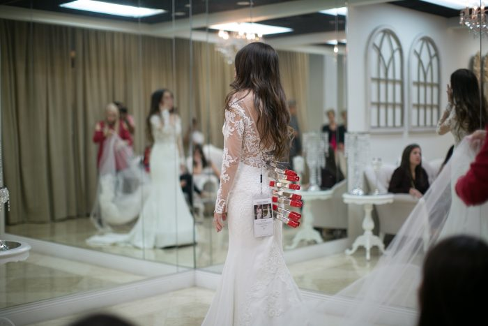 Bride Trying on Wedding Dress at Boutique and Wearing Clamps for Alterations