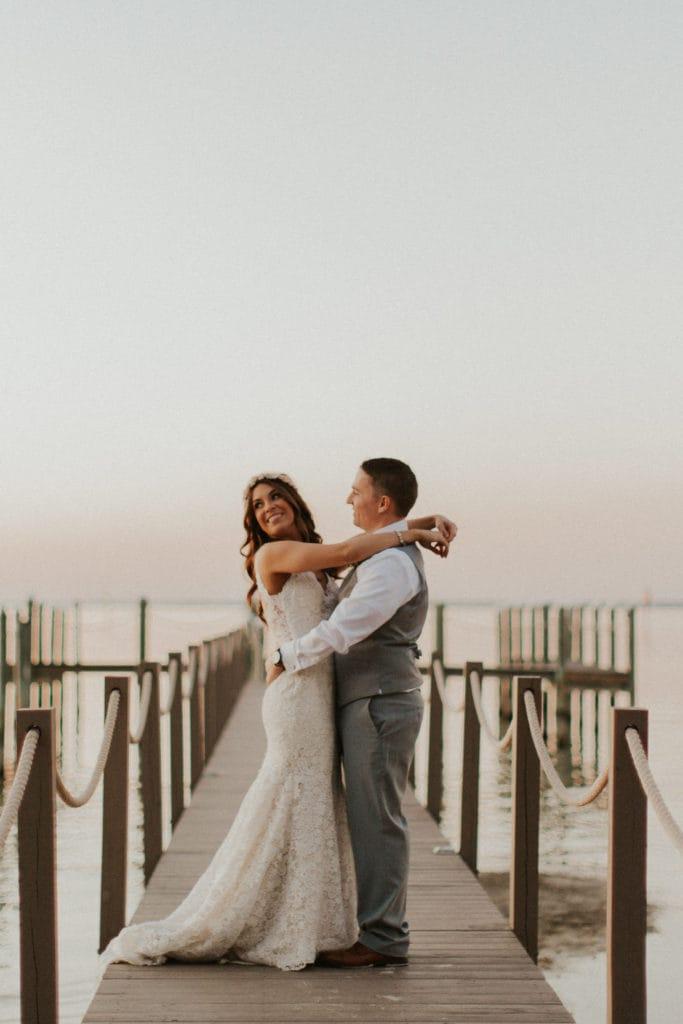 Groom on Pier Hugging Real Bride Wearing Affordable Boho Wedding Dress Called Hope by Rebecca Ingram