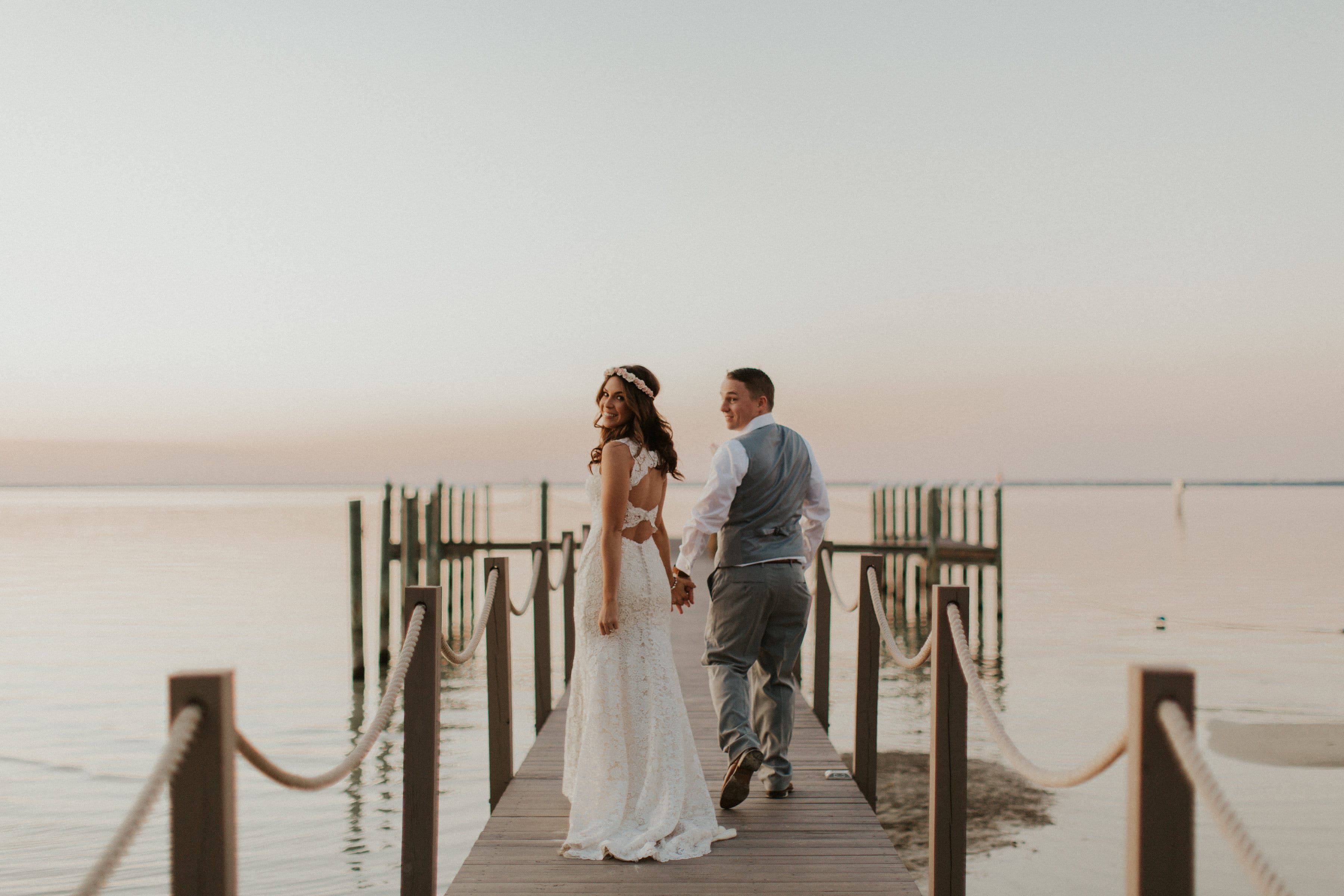 Bride and Groom From the Back Walking on Pier After Their Wedding Ceremony