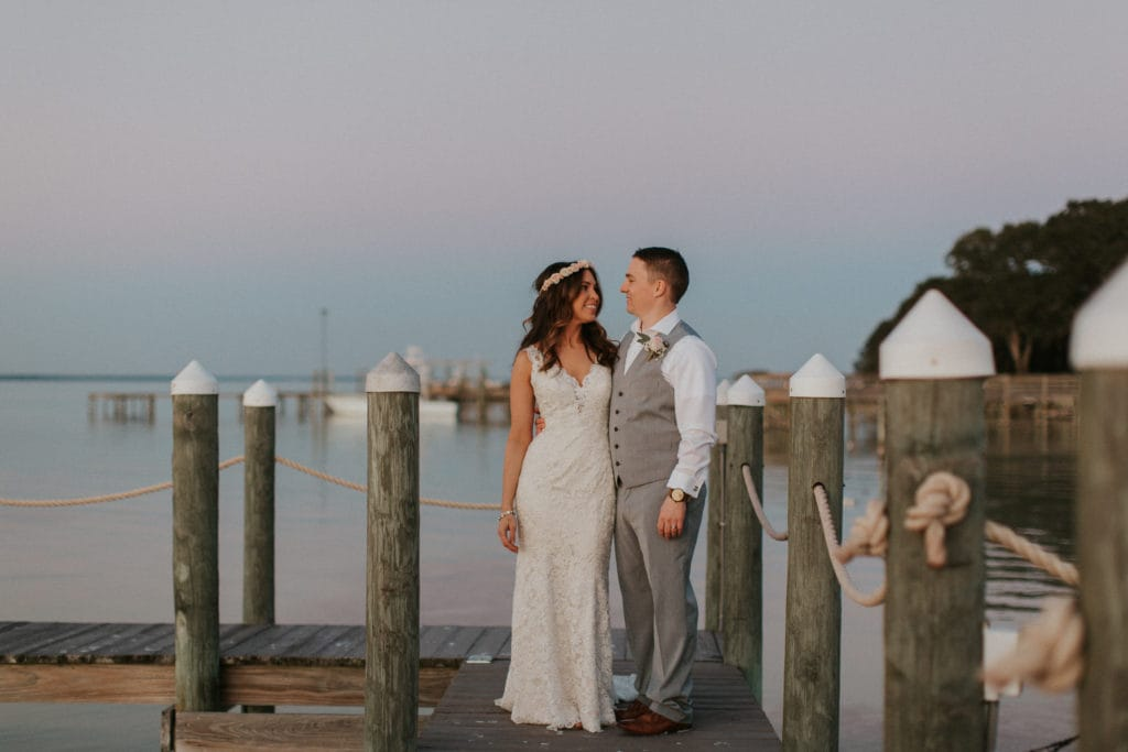 Groom on Pier Standing with Real Bride Wearing Affordable Wedding Dress Called Hope by Rebecca Ingram
