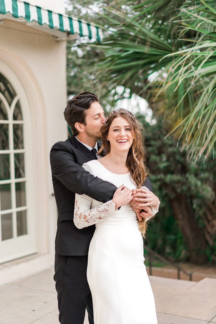 Groom with Bride Wearing Long Sleeve Sheath Wedding Gown Called Olyssia by Maggie Sottero