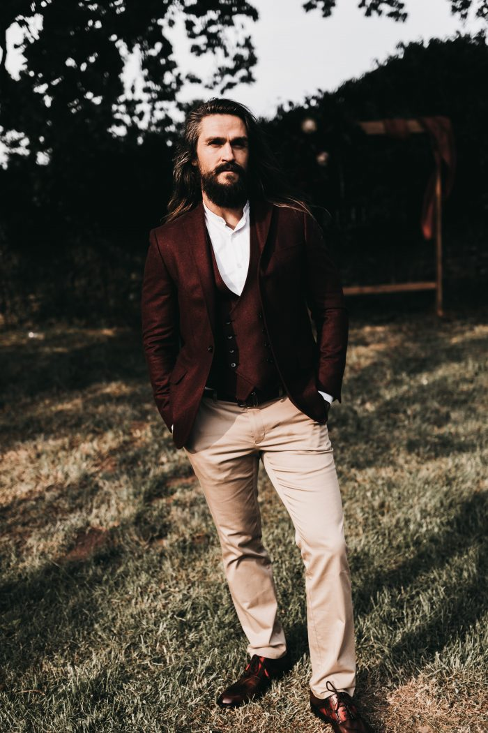 Groom with Long Hair Wearing Burgundy Suit Coat with Khakis for Halloween Wedding Ideas