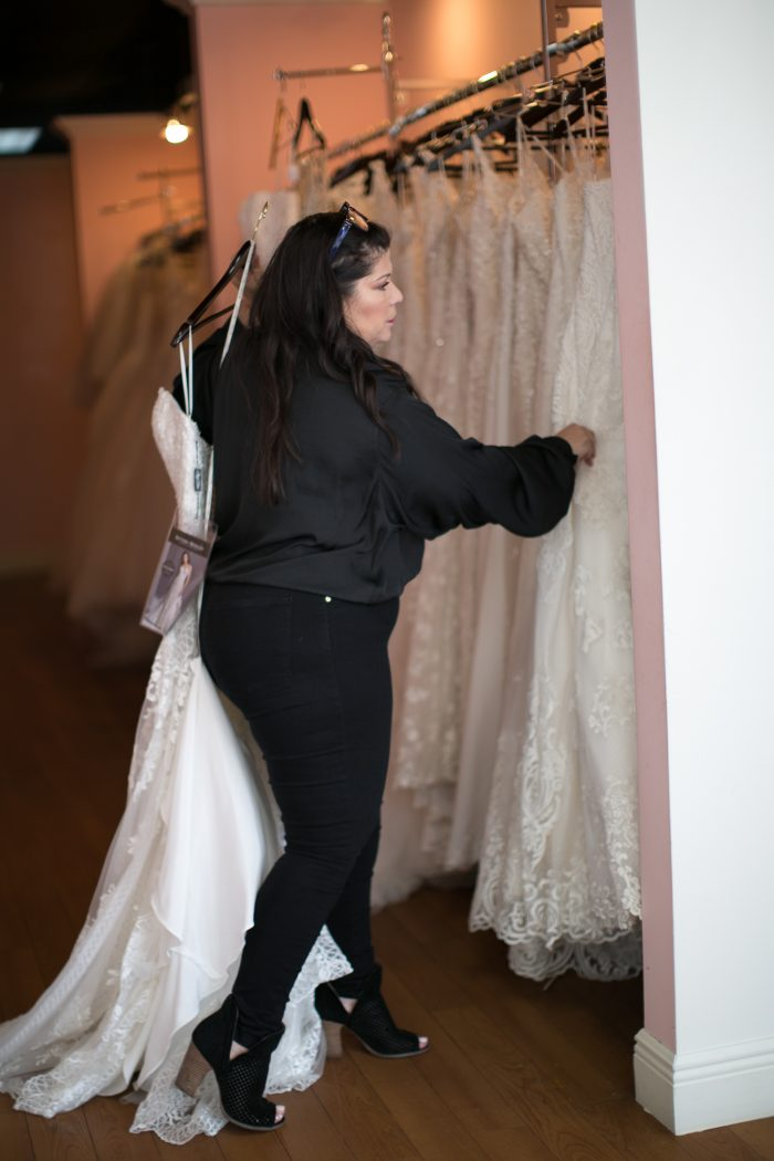 Bridal Stylist Pulling Wedding Dresses Off the Rack for Bride to Try On
