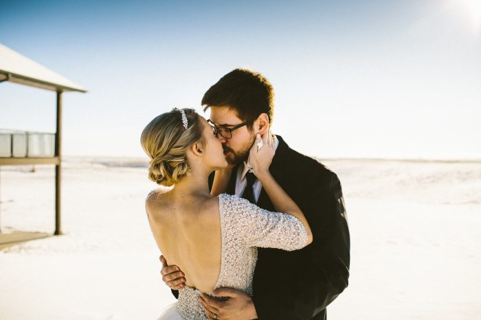 Groom Kissing Bride Wearing Ball Gown Wedding Dress called Allen by Sottero and Midgley at Winter Wedding