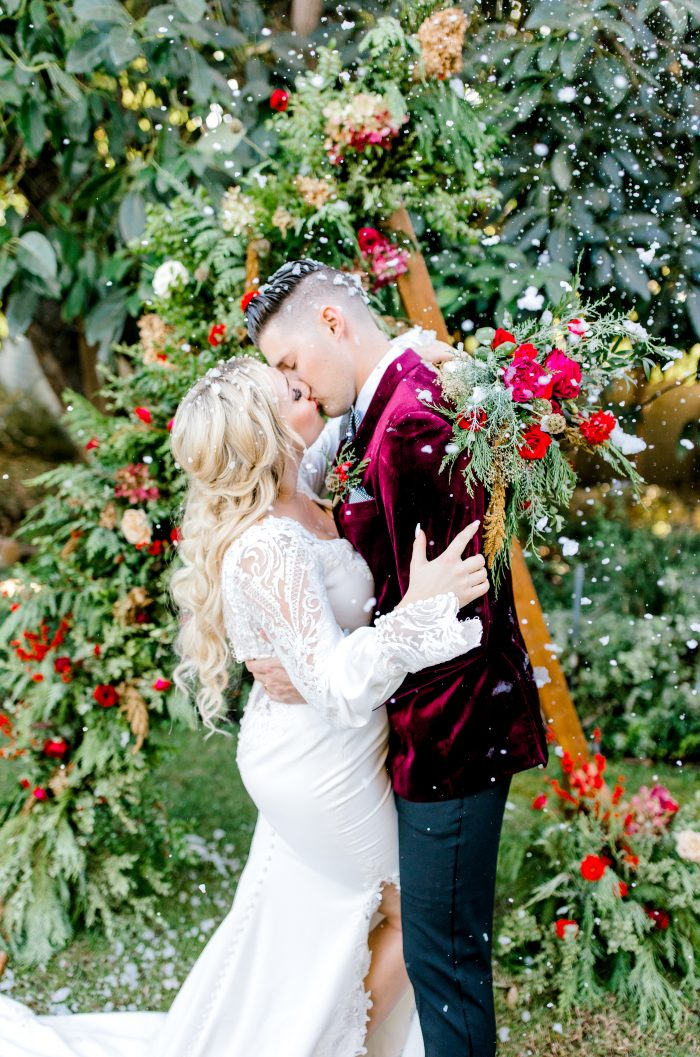 Groom in Ruby Suit Kissing Bride Wearing Crepe Bishop Sleeve Wedding Dress Called Armante by Sottero and Midgley
