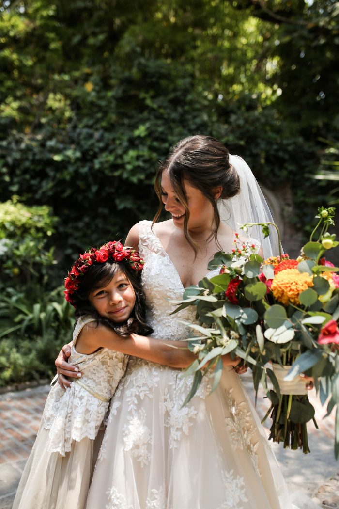 Real Bride at Destination Wedding in Mexico Hugging Little Mexican Flower Girl