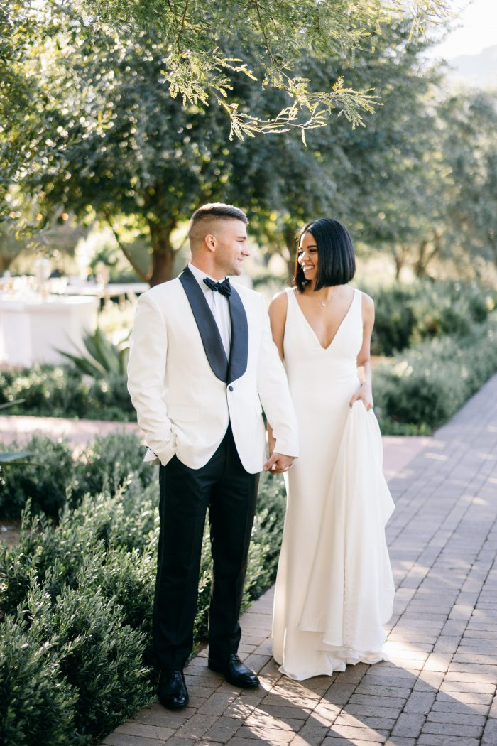 Groom in Mid-Century Modern White Suit with Bride Wearing Simple Wedding Dress Called Fernanda by Maggie Sottero