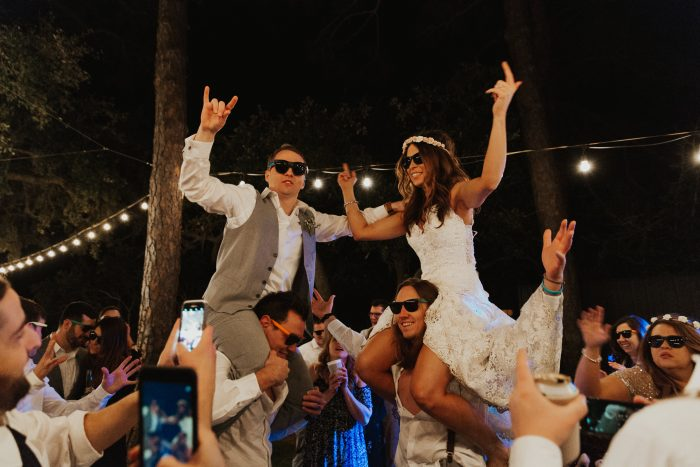 Bride and Groom Getting Carried on Shoulders at Wedding Party