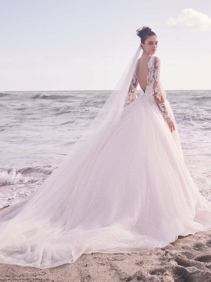Bride on Beach Wearing Bishop Sleeve Wedding Dress with Detachable Lace Overskirt Called Bellamy by Sottero and Midgley