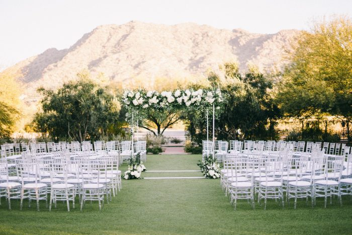 Wedding Arch in Green and White Florals Surrounded by White Chairs at Outdoor Wedding Ceremony