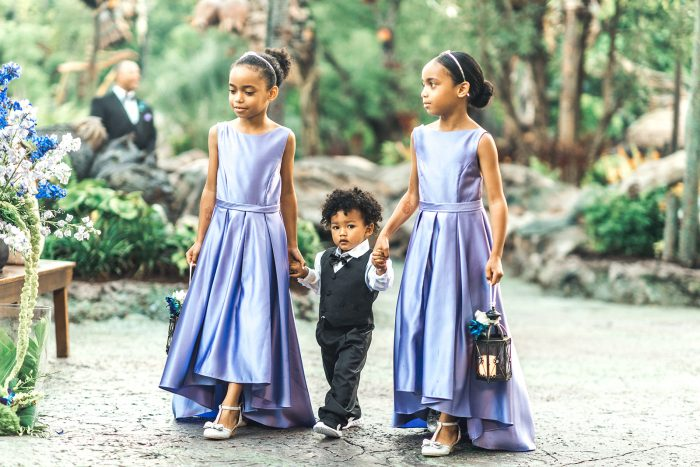 Flower Girls Wearing Purple Dresses Walking with Little Ring Bearer at Fairytale Wedding