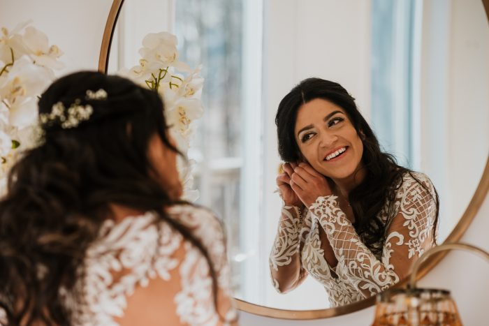 Real Bride Getting Ready in the Mirror While Wearing Slinky Lace Wedding Dress Called Dakota by Sottero and Midgley