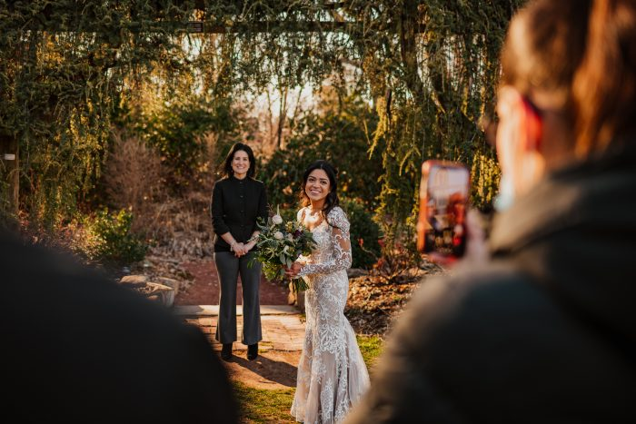 Bride Standing by Officiant During Wedding Ceremony While Guests Are Social Distancing