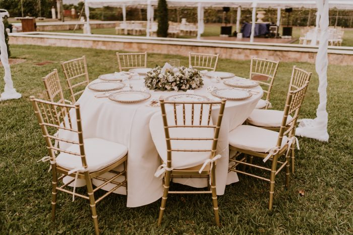 Round Table Covered with White Cloth and Gold Chairs at Backyard Wedding to Help Guests Social Distance