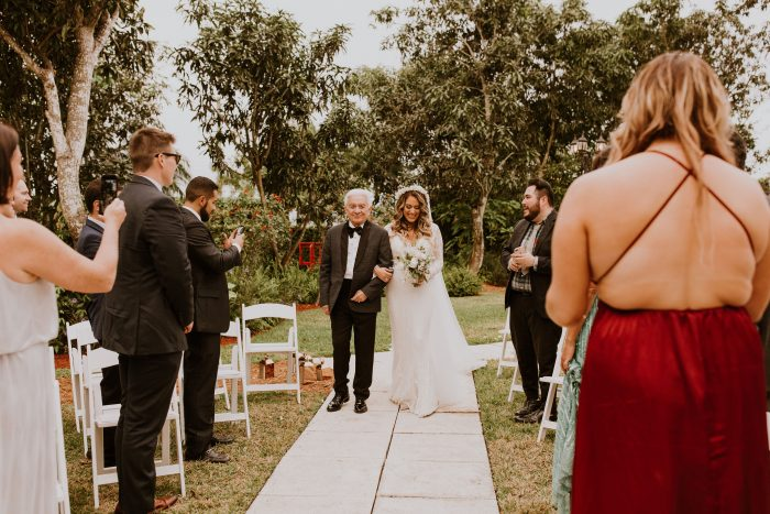Father of the Bride Walking Bride Down the Aisle During Backyard Wedding While Guests are Social Distancing