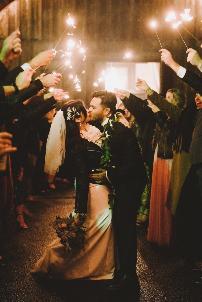 Real Bride Wearing Maggie Sottero Wedding Dress and Kissing Groom While Guests Wave Sparklers After Reception