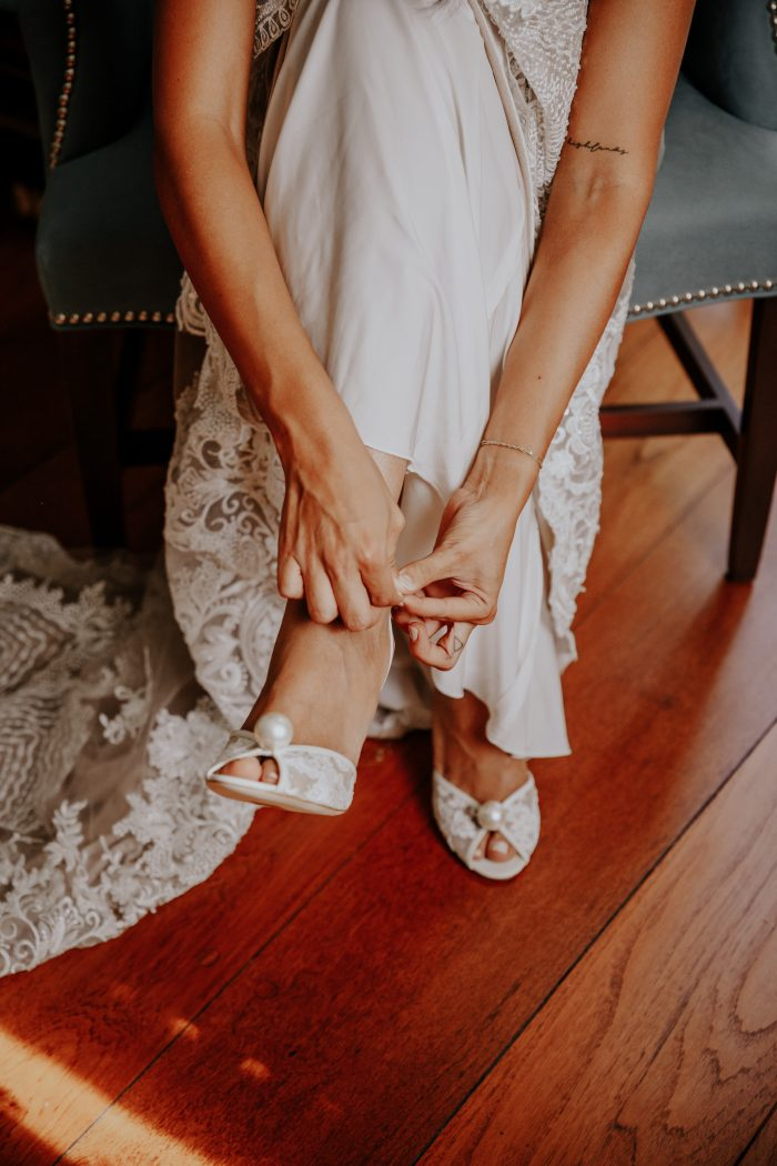 Bride Putting on Pearl Accented Open Toe Shoes for Wedding