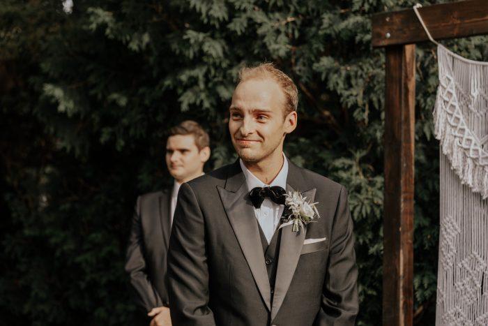 Groom Watching Bride Walk Down the Aisle at Boho-Chic Backyard Elopement