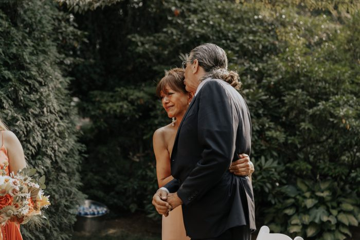 Mother and Father of Bride Watching Bride's Ceremony During Backyard Elopement