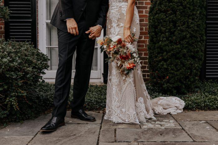 Groom with Bride Wearing Boho Wedding Dress and Holding Colorful Boho Wedding Bouquet