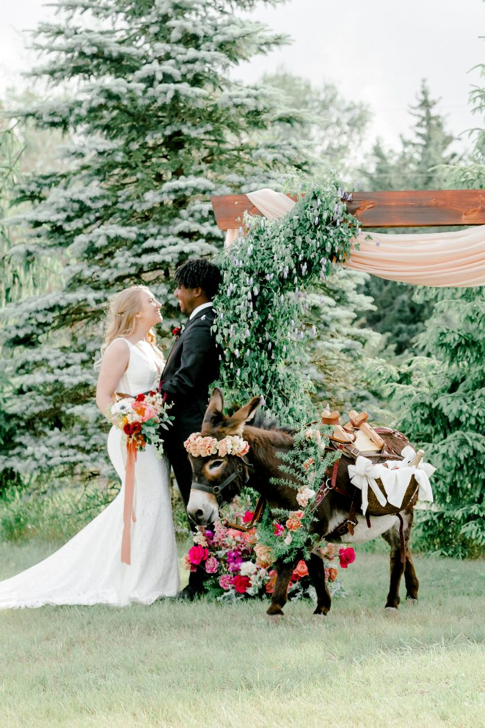 Bride and Groom at Intimate Wedding Ceremony with Colorful Florals and Unique Donkey under an Archway
