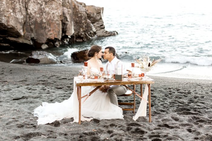 Bride and Groom on Black Sand Beach Looking at Each Other and Sitting at a Reception Table