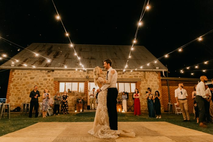 Bride and Groom Dancing Under DIY Fairy Lights While Brides Wearing Sottero and Midgley Wedding Dress
