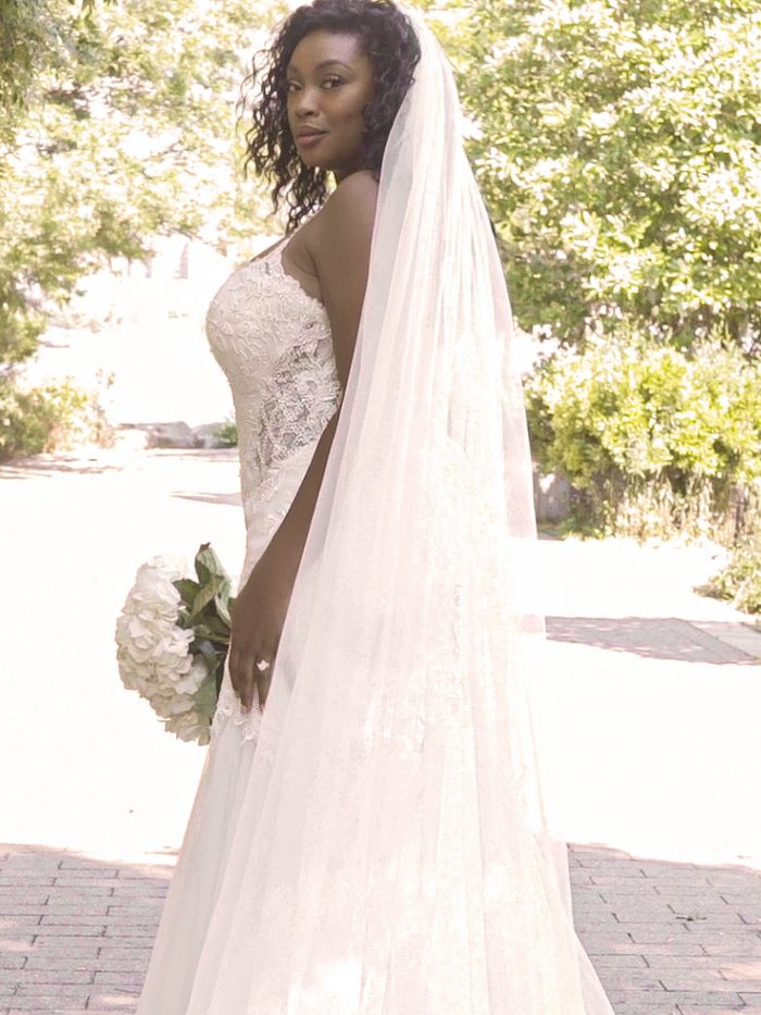 Black Plus Size Model Wearing Fit-and-Flare Wedding Dress with Long Tulle Wedding Veil Called Halle by Maggie Sottero